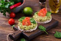 Τραγανό ψωμί σάντουιτς με το guacamole και ντομάτες σε ένα ξύλινο υπόβαθρο Στοκ Εικόνα