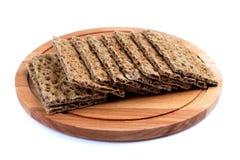 Τραγανό ψωμί σε έναν ξύλινο δίσκο, που απομονώνεται Στοκ Φωτογραφία