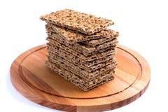 Τραγανό ψωμί σε έναν ξύλινο δίσκο, που απομονώνεται Στοκ Εικόνες
