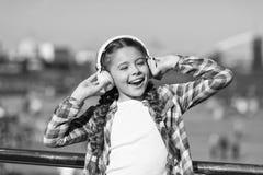Τραγουδήστε την ευτυχία Ευτυχή ακουστικά ένδυσης παιδιών Λίγος οπαδός μουσικής r Το μικρό κορίτσι ακούει τη μουσική υπαίθρια στοκ φωτογραφία με δικαίωμα ελεύθερης χρήσης
