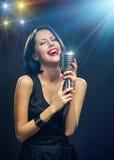 Τραγουδιστής με τις ιδιαίτερες προσοχές που κρατούν mic στο φωτισμένο υπόβαθρο στοκ φωτογραφία