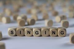 Τραγουδώντας - κύβος με τις επιστολές, σημάδι με τους ξύλινους κύβους Στοκ Φωτογραφίες
