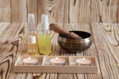 Τραγουδώντας κύπελλο στο ξύλινο υπόβαθρο Καίγοντας κεριά και πετρέλαιο για aromatherapy και το μασάζ Στοκ Φωτογραφία