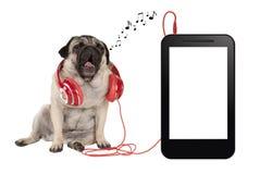 τραγουδώντας σκυλί κουταβιών μαλαγμένου πηλού με τα κόκκινα ακουστικά, καθμένος δίπλα στο κενή τηλέφωνο ή την ταμπλέτα Στοκ φωτογραφία με δικαίωμα ελεύθερης χρήσης