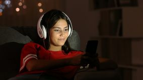 Τραγούδι εφήβων που ακούει τη μουσική με τα ακουστικά και το τηλέφωνο απόθεμα βίντεο