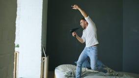 Τραγούδι νεαρών άνδρων στο στεγνωτήρα τρίχας και χορός rocknroll στο κρεβάτι στην κρεβατοκάμαρα στοκ φωτογραφία