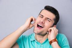 Τραγούδι νεαρών άνδρων στα ακουστικά Στοκ φωτογραφία με δικαίωμα ελεύθερης χρήσης