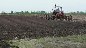 Τρακτέρ με έναν καλλιεργητή στο χώμα απόθεμα βίντεο