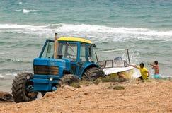 Τρακτέρ που ανακτά μια βάρκα από το καταβρέχοντας νερό Στοκ Εικόνα