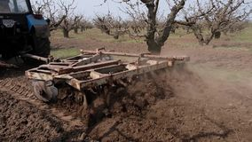 Τρακτέρ που καλλιεργεί το έδαφος με έναν βωλοκόπο δίσκων στον κήπο φρούτων φιλμ μικρού μήκους