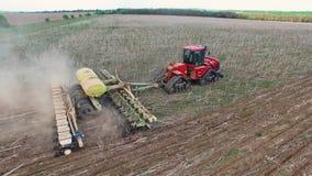 Τρακτέρ που προετοιμάζει το έδαφος για τη σπορά της κεραίας δέκα έξι σειρών, έννοια της καλλιέργειας, της σποράς, του οργώνοντας  φιλμ μικρού μήκους