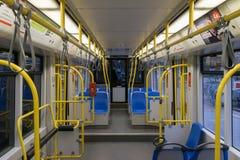 Τραμ μέσα, εσωτερικό μεταφορών πόλεων με τις μπλε κίτρινες λαβές καθισμάτων, τα φωτεινά φω'τα και το κλιματιστικό μηχάνημα στοκ φωτογραφία