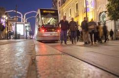 Τραμ που τρέχει εμπρός κεντρικός τη νύχτα με το ντεκόρ Χριστουγέννων Στοκ Εικόνες