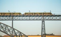Τραμ του μετρό που πηγαίνουν μέσω των DOM Luise Ι γέφυρα μεταξύ του Πόρτο και της Βίλα Νόβα ντε Γκάια στοκ εικόνες