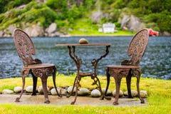 Τραπεζάκι σαλονιού με την υπαίθρια κοντινή λίμνη δύο καρεκλών Στοκ Εικόνες