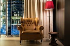 Τραπεζάκι σαλονιού πολυθρόνων δέρματος και λαμπτήρας πατωμάτων στο λόμπι στο ξενοδοχείο Στοκ Εικόνες