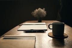 Τραπεζάκι σαλονιού με το φλιτζάνι του καφέ που καπνίζει στη καφετερία Χαλάρωση στη καφετερία κλείστε επάνω Στοκ Εικόνες