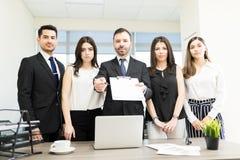 Τραπεζίτες που παρουσιάζουν το νέο σχέδιο να υπογράψει στοκ εικόνα