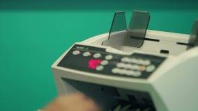 Τραπεζίτης που μετρά τα χρήματα με τον αυτόματο μετρητή απόθεμα βίντεο