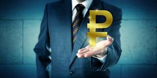 Τραπεζίτης που προσφέρει ένα χρυσό ρωσικό σύμβολο ρουβλιών Στοκ Φωτογραφίες