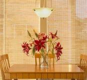 Τραπεζαρία εγχώριων εσωτερική κουζινών με τον ξύλινες πίνακα και τις καρέκλες, το ανάβοντας προσάρτημα, τα φρέσκα λουλούδια και τ στοκ εικόνα