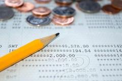 Τραπεζικός λογαριασμός βιβλιάριων απολογισμού αποταμίευσης και μολύβι και αφηρημένο υπόβαθρο νομισμάτων Στοκ Φωτογραφία