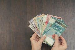 Τραπεζογραμμάτια έξι νομισμάτων της Νοτιοανατολικής Ασίας στα θηλυκά χέρια Έννοια τραπεζικών εργασιών και ταξιδιού Στοκ εικόνα με δικαίωμα ελεύθερης χρήσης