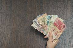 Τραπεζογραμμάτια έξι νομισμάτων της Νοτιοανατολικής Ασίας στα θηλυκά χέρια Έννοια τραπεζικών εργασιών και ταξιδιού Στοκ Φωτογραφίες