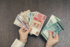 Τραπεζογραμμάτια έξι νομισμάτων της Νοτιοανατολικής Ασίας στα θηλυκά χέρια Έννοια τραπεζικών εργασιών και ταξιδιού Στοκ Εικόνα