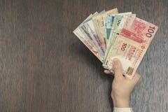 Τραπεζογραμμάτια έξι νομισμάτων της Νοτιοανατολικής Ασίας στο θηλυκό χέρι Έννοια τραπεζικών εργασιών και ταξιδιού Στοκ Φωτογραφία