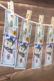 Τραπεζογραμμάτια αμερικανικών δολαρίων που κρεμούν στο σχοινί στο ξύλινο υπόβαθρο για την έννοια ξεπλύματος χρημάτων στοκ φωτογραφία με δικαίωμα ελεύθερης χρήσης