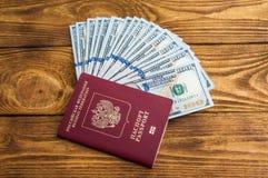 Τραπεζογραμμάτια δολαρίων στον ανεμιστήρα και το διαβατήριο στο ξύλι στοκ εικόνες