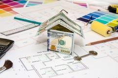 Τραπεζογραμμάτια δολαρίων ως πρότυπο σπίτι σε ένα σχέδιο κατασκευής Στοκ Φωτογραφίες