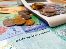 Τραπεζογραμμάτια και νομίσματα της Μαλαισίας RINGGIT με τον υπολογιστή στοκ εικόνες