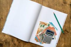 Τραπεζογραμμάτια και υπολογιστής με το σημειωματάριο στοκ εικόνες