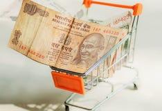 Τραπεζογραμμάτια με τον ινδικό ηγέτη Mahatma Γκάντι μέσα στο καροτσάκι λεωφόρων αγορών Ιδέα της καταναλωτικής δυνατότητας στη σύγ Στοκ Φωτογραφίες