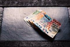 Τραπεζογραμμάτια σε ένα υπόβαθρο πετρών Ευρο- τραπεζογραμμάτια χρημάτων της διαφορετικής αξίας ζωηρόχρωμα ευρο- ευρωπαϊκά χρήματα στοκ φωτογραφία