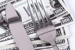 Τραπεζογραμμάτιο δολαρίων κάτω από το μαχαίρι και το δίκρανο Στοκ Φωτογραφία