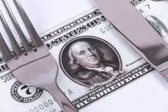 Τραπεζογραμμάτιο δολαρίων κάτω από το μαχαίρι και το δίκρανο Στοκ Εικόνες