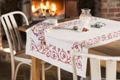 Τραπεζομάντιλο με το κόκκινο Floral σχέδιο στον πίνακα που καίγεται πλησίον Fireplac Στοκ Εικόνες