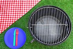 Τραπεζομάντιλο πικ-νίκ, πιάτο, δίκρανο, μαχαίρι, BBQ σχάρα στο χορτοτάπητα Στοκ Φωτογραφία