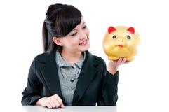 τραπεζών ευτυχείς νεολαίες γυναικών εκμετάλλευσης piggy Στοκ Εικόνα