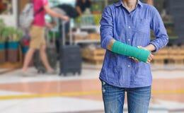 Τραυματισμένη γυναίκα με πράσινο χυτό σε διαθεσιμότητα και βραχίονας στον ταξιδιώτη στο mot Στοκ Φωτογραφίες