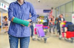 Τραυματισμένη γυναίκα με πράσινο χυτό σε διαθεσιμότητα και βραχίονας στον ταξιδιώτη στο mot Στοκ φωτογραφία με δικαίωμα ελεύθερης χρήσης