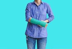 Τραυματισμένη γυναίκα με πράσινο χυτό σε διαθεσιμότητα και βραχίονας στο μπλε υπόβαθρο Στοκ φωτογραφία με δικαίωμα ελεύθερης χρήσης