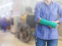 Τραυματισμένη γυναίκα με πράσινο χυτό σε διαθεσιμότητα και βραχίονας στην αφηρημένη θαμπάδα χ Στοκ Φωτογραφίες