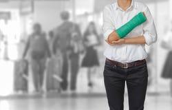 Τραυματισμένη γυναίκα με πράσινο χυτό σε διαθεσιμότητα και βραχίονας στον ταξιδιώτη στο mot Στοκ Φωτογραφία