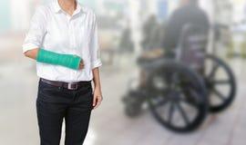 Τραυματισμένη γυναίκα με πράσινο χυτό σε διαθεσιμότητα και βραχίονας στο λευκό Στοκ Εικόνα