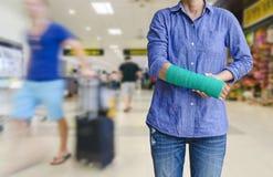 Τραυματισμένη γυναίκα με πράσινο χυτό σε διαθεσιμότητα και βραχίονας στον ταξιδιώτη στο mot Στοκ εικόνα με δικαίωμα ελεύθερης χρήσης