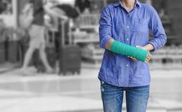 Τραυματισμένη γυναίκα με πράσινο χυτό σε διαθεσιμότητα και βραχίονας στον ταξιδιώτη στο mot Στοκ εικόνες με δικαίωμα ελεύθερης χρήσης